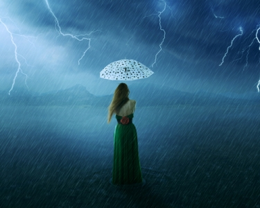 woman in green dress under umbrella on countryside flooded field