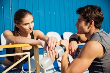 Close up portrait of a young couple talking on athletics track f