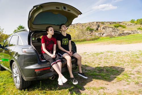 Arguing Couple Sitting on Tailgate of Car by Road