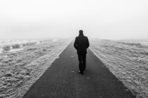 Man walking on an empty desolate raod