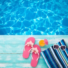 Summer Holidays in Beach Seashore. Fashion accessories summer flip flops, hat, sunglasses on bright turquoise board near the pool